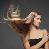beautiful-model-with-long-smooth-flying-blonde-hair-isolated-on-dark-grey-studio-background-young-caucasian-model-with-well-kept-skin-and-hair-blowing-on-air-scaled.jpg